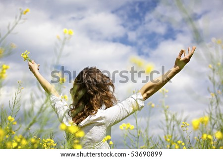 Young woman standing in yellow rapeseed field raising her arms expressing gratitude or freedom, view from behind. - stock photo