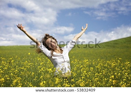 Young woman standing in yellow rapeseed field raising her arms expressing happiness or freedom.
