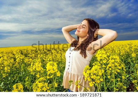 Young woman standing in yellow rapeseed field, relaxing and smiling at the sun and! Blue sky background! - stock photo