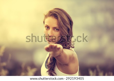 Young woman standing in yoga pose with straight hands. Freedom and relax concept. Toned image - stock photo