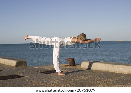 Young woman standing in yoga position next to the sea - stock photo