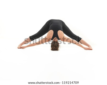 young woman standing in yoga posture, dressed in black, on white background - stock photo