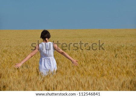 Young woman standing jumping and running  on a wheat field with blue sky in  background at summer day representing healthy life and agriculture concept - stock photo