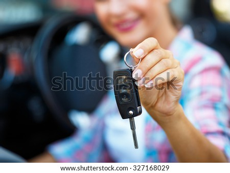 Young woman standing near a convertible with keys in hand - concept of buying a used car or a rental car - stock photo