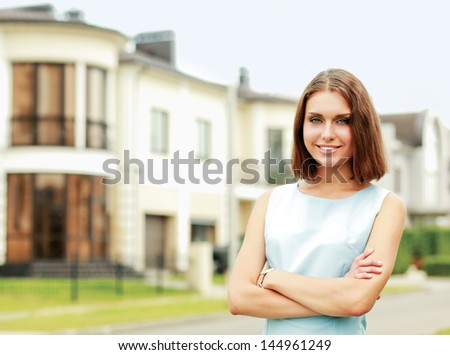 Young woman standing near house - stock photo