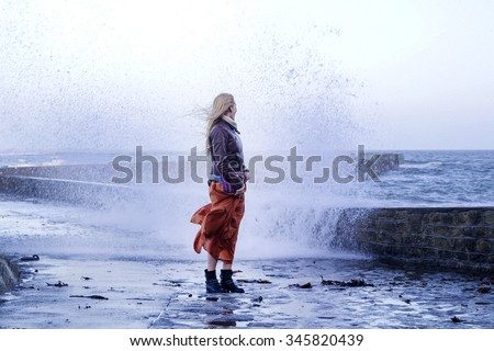 Young woman standing near the big wave on the pier in France, autumn winter storm - stock photo