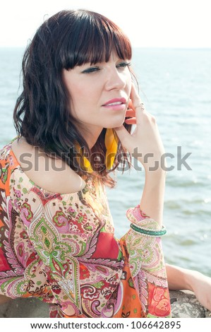 Young woman standing near the shore, looking rested and relaxed - stock photo