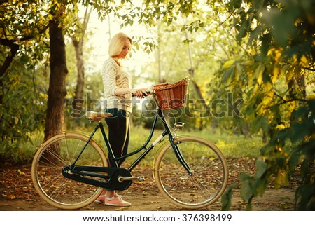 Young Woman Standing near Vintage Bicycle with Basket in Park at the Sunset. Selective Focus on Bike, Woman Blurred, Image Toned with Retro Colors. - stock photo