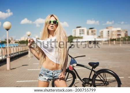 Young woman standing next to black bicycle. Outdoor lifestyle portrait of cool girl.