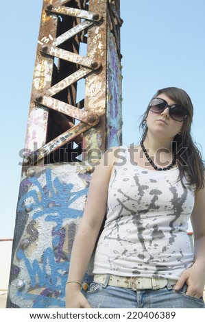 Young woman standing next to graffitied metal tower