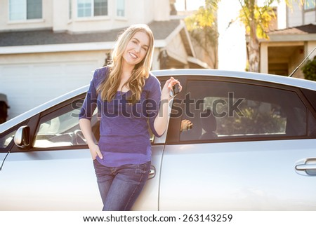 Young woman standing next to her car - stock photo