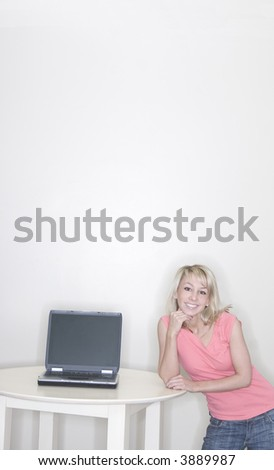 Young woman standing next to her laptop while she smiles and grins wearing a pink t-shirt