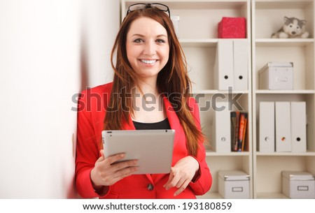 young woman standing next wardrobe with folders with tablet - stock photo
