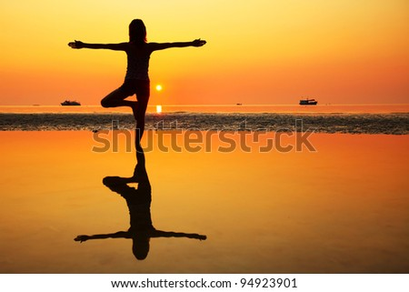 Young woman standing on a beach and doing exercises - stock photo