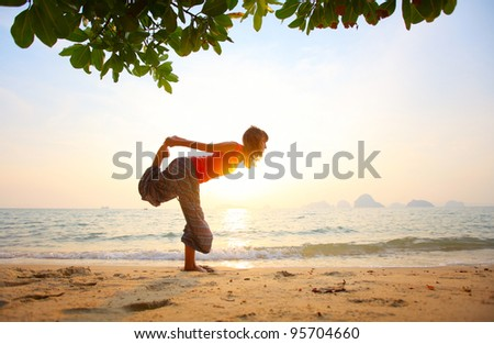Young woman standing on a beach and doing yoga exercices - stock photo