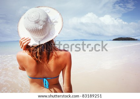 Young woman standing on a beach holding her straw hat and looking to the horizon. - stock photo