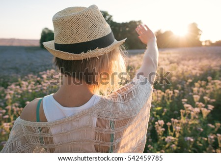 Young woman standing on a field with sunrise on the background