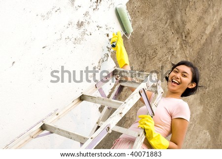 young woman standing on a ladder, painting exterior wall of her house - stock photo