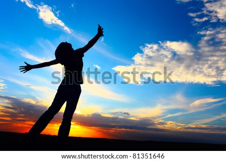 Young woman standing on a meadow on sunset background and looking to a sky with raised hands. - stock photo