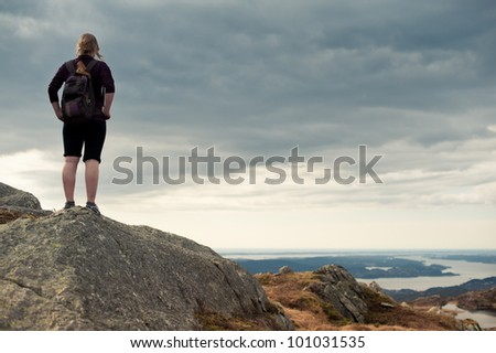 Young woman standing on a rock and looking to a valley below - stock photo