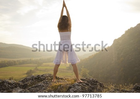 Young woman standing on a rock greeting the light of the sun
