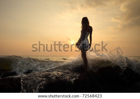 Young woman standing on a rock in sea and holding her dress - stock photo