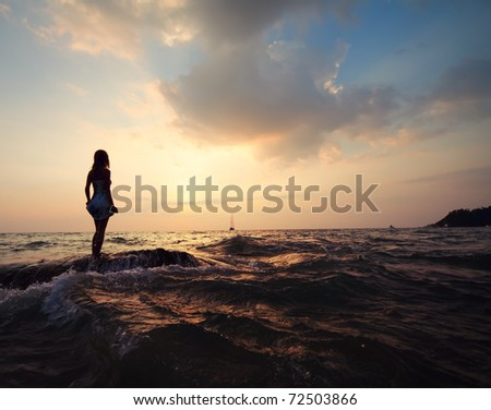Young woman standing on a rock in sea holding her dress and looking to a horizon - stock photo