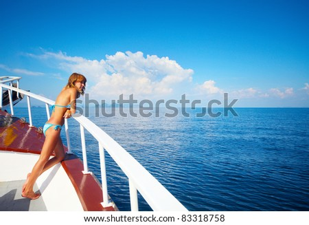 Young woman standing on a ship's board and looking to a horizon