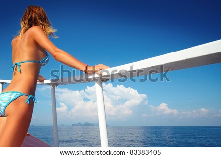 Young woman standing on a ship's board and looking to a horizon - stock photo
