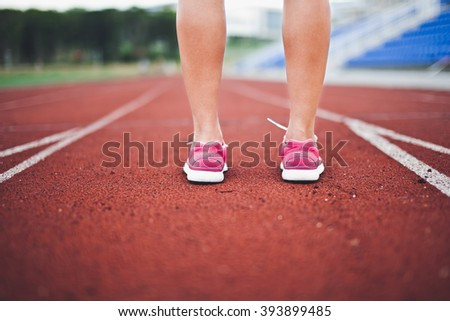 Young woman standing on a stadium running track preparing for run during training. Close-up calves view. Perspective view on stadium