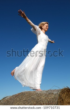 Young woman standing on a straw bale against a blue sky - stock photo