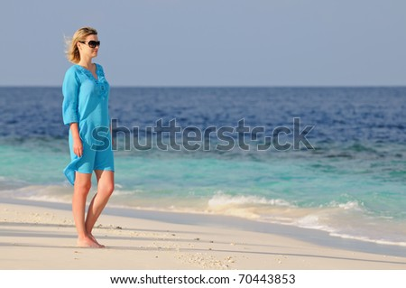 Young woman standing on a tropical beach against sea