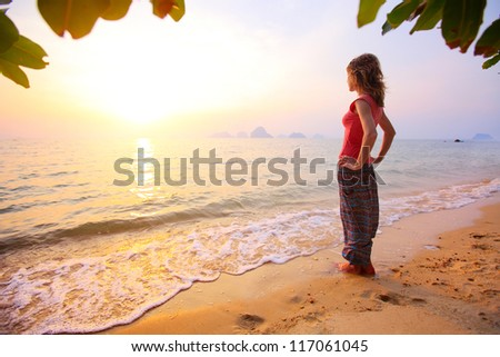 Young woman standing on a tropical beach and looking to a sea - stock photo