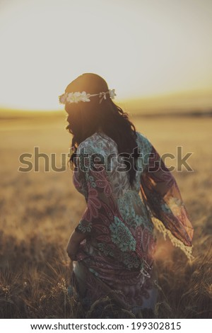 Young woman standing on a wheat field with sunrise on the background - stock photo