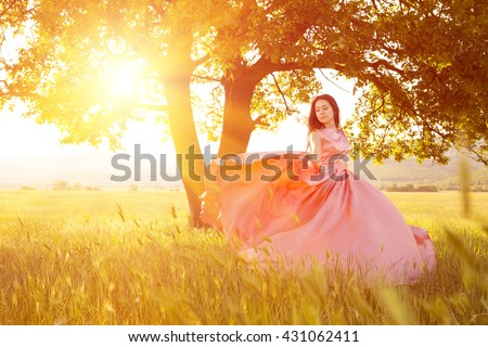Young woman standing on a wheat field with sunrise on the background. Beauty Romantic Girl Outdoors. The dress fluttering in the wind at sunset. flying fabric. - stock photo