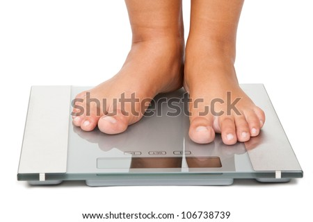 Young woman standing on bathroom scales - stock photo