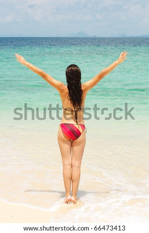 Young woman standing on beach with arms raised - stock photo