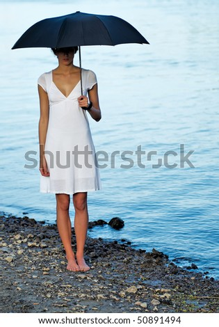 Young woman standing on beach with umbrella