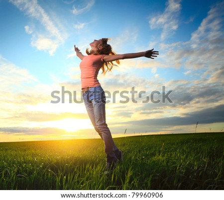Young woman standing on countryside meadow with raised hands