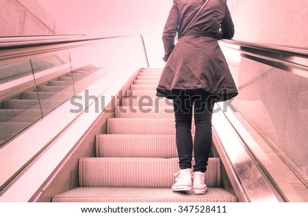 Young woman standing on escalators stairway with back light contrast - Modern urban travel concept - Vintage filtered look with soft desaturated marsala color tones and sunshine halo flare - stock photo