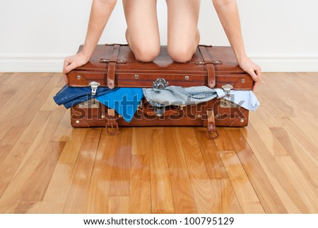 Young woman standing on her knees on overfilled suitcase, trying to close it. - stock photo