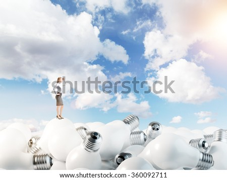 Young woman standing on huge scattered bulbs and looking forward. Blue sky at the background. Concept of new ideas. - stock photo