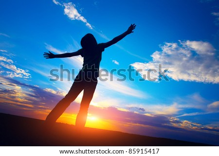 Young woman standing on meadow on sunset sky background - stock photo