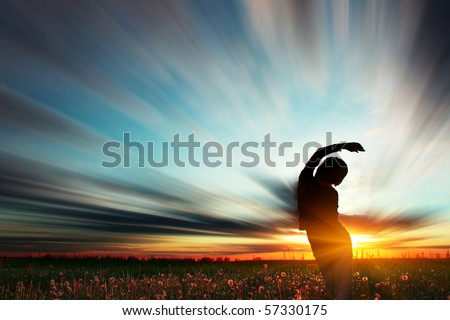 Young woman standing on meadow with herbs under sunset lights - stock photo
