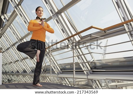 Young woman standing on one leg in a tree pose - stock photo