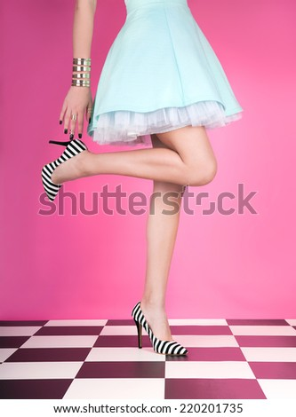 Young woman standing on one leg wearing high heels - stock photo