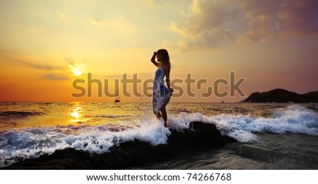 Young woman standing on rock in sea and looking to somewhere - stock photo