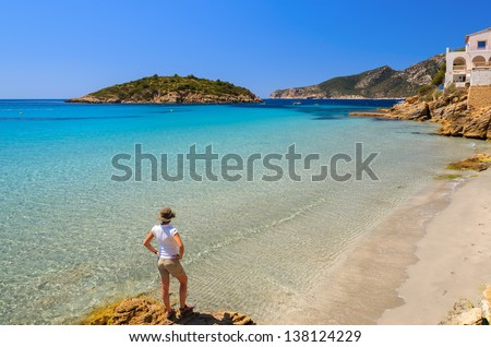 Young woman standing on rock looking at beautiful beach with turquoise sea water, Sant Elm, Mallorca island, Spain - stock photo
