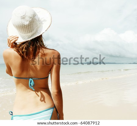 Young woman standing on sand near sea and holding a hat - stock photo