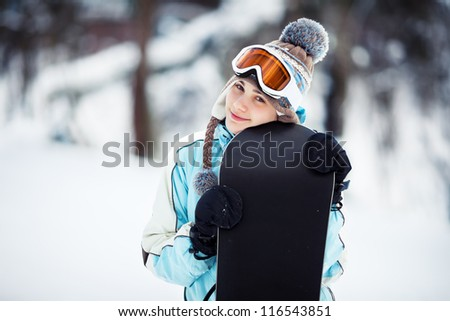 Young woman standing on ski slope and leaning on her snowboard, she's looking at camera and smiling, copy space, close up - stock photo